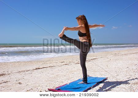 Woman Doing Yoga Exercise Standing Hand To Toe Posture On Beach