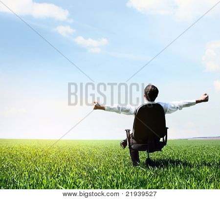 Young man with raised hands sitting in char on green meadow and looking to a sky with clouds