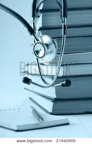 A stethoscope on a pile of books, notebook, pen