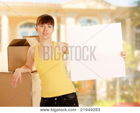 A woman is holding a blank standing with boxes outside