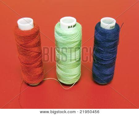 three bobbin threads on red