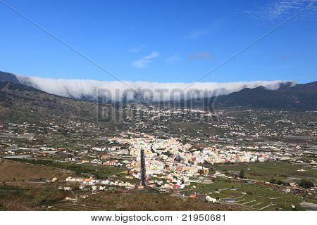 La Palma, Canary Islands. Photo shows the rare and famous cloud phenomena where clouds are falling down over the mountain ridge Cumbre Nueva like a waterfall. Also showing city Los Llanos de Aridane