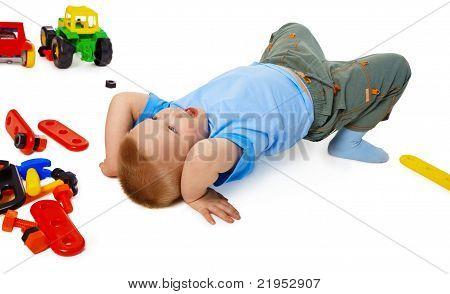 Kind auf dem Boden unter dem Spielzeug zum Narren