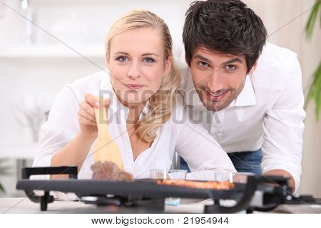 Couple cooking steak and prawns on a table top hotplate