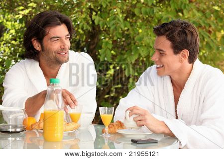 Two men housemates having breakfast outdoors