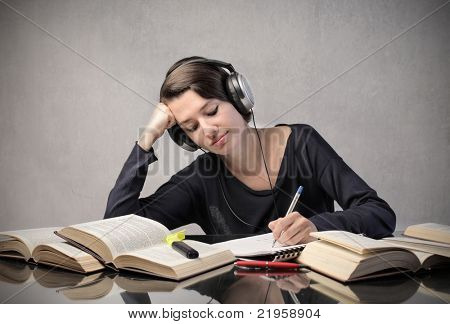 Smiling student listening to music while revising
