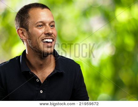 young man laughing against a plants background