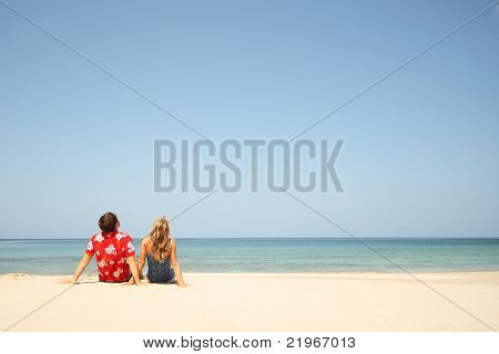 Young couple sitting on a sand by sea and looking to a blue clear sky