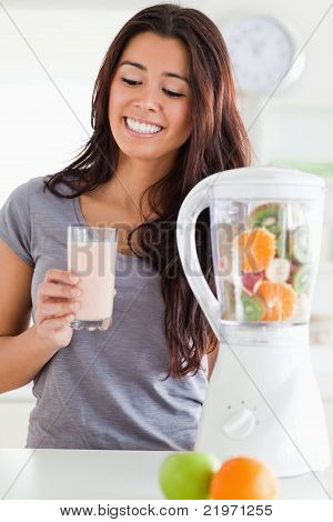 Good Looking Woman Using A Blender While Holding A Drink