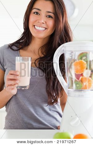 Charming Woman Using A Blender While Holding A Drink