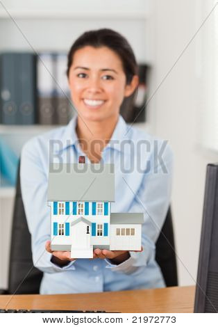 Gorgeous Woman Holding A Miniature House While Looking At The Camera