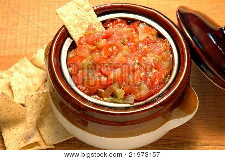 Salsa bowl with corn chips on a rustic table