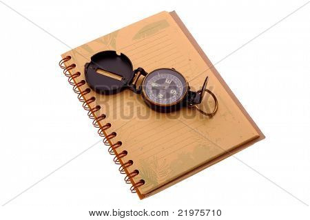 Compass siting on an open notebook isolated over white
