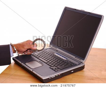 Laptop computer with business mans hand in handcuffs