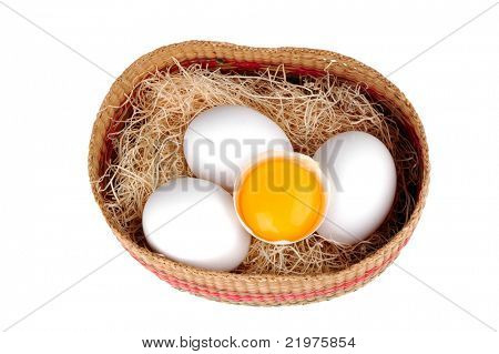 Basket with eggs and straw with one cracked egg isolated over white