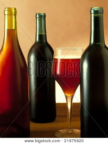 Three Red Wine bottles without labels & Wine Glass on a wooden table