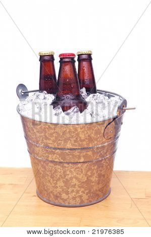 Three Beer Bottles in Bucket on Wood Table and White Background