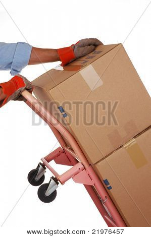 Man With Work Gloves Pushing Stack of Moving Boxes on Hand Truck isolated over white