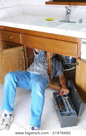 Homem com corpo metade sob o armário de pia e chegando de chave na caixa de ferramentas
