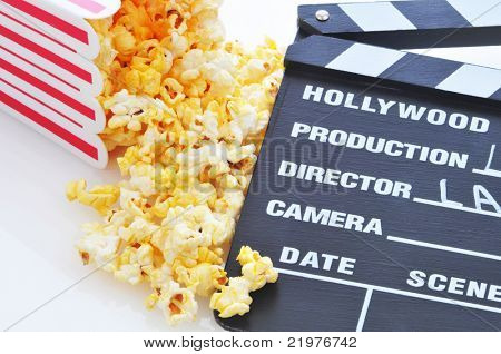 Movie clapboard with popcorn spill on white
