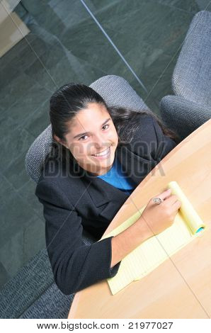 Smiling officeworker taking notes at a conference table seen from above