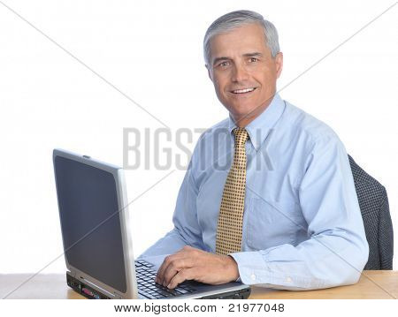 Middle Aged Businessman Seated at His Desk with Laptop Computer isolated on white