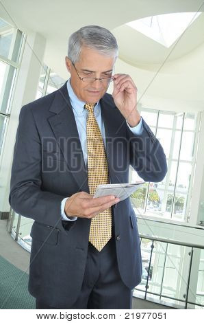 Middle Aged Businessman Standing in Modern Office Setting Reading Newspaper