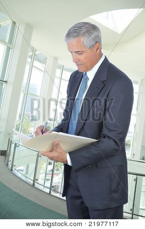 Standing Middle Aged Businessman Writing in File Folder in Office Setting