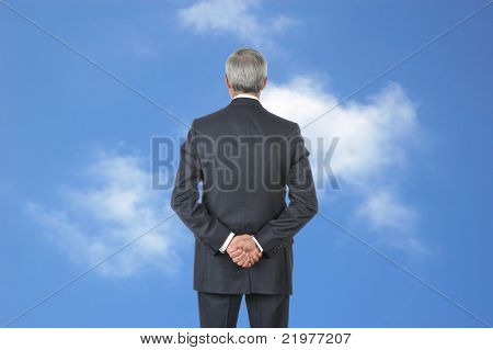 Middle Aged Business with hands behind back standing in front of blue cloudy sky
