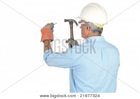 Rear View of Middle Aged Construction Worker With Hammer and Nail isolated on white
