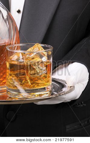 Waiter in tuxedo holding Cocktail and Decanter on tray vertical format torso only
