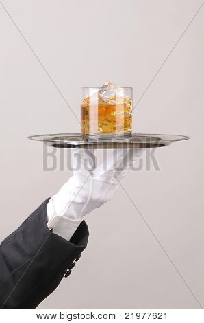 Waiter in tuxedo Presenting Cocktail on silver tray closeup vertical format hand and arm only