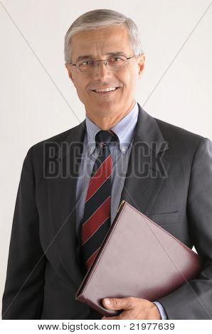 Middle Aged Businessman with Leather Folder under his arm over light gray background vertical format