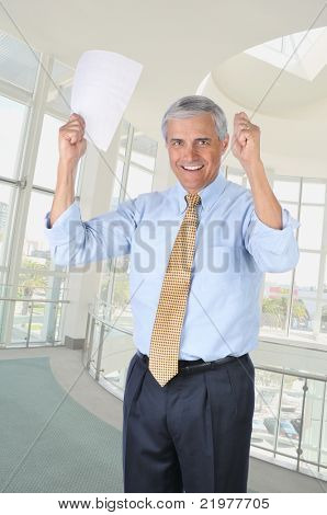 Happy Middle Aged Businessman In Office Holding a Contract in his Hands that are Raised in a victory gesture vertical format