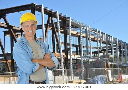 Construction worker with arms crossed on job site standing in front of new building frame. Horizontal format with man smiling at camera.
