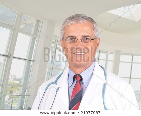 Close up portrait of a smiling middle aged doctor in lab coat with stethoscope around his neck. Horizontal format in modern office setting.
