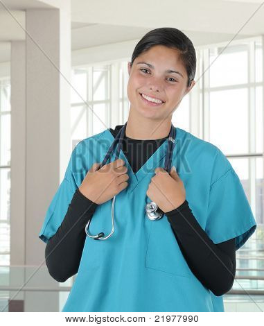 Smiling female medical professional in modern medical office wearing scrubs holding stethoscope around her neck. Vertical format.