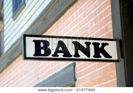 Close up of an old wooden bank sign with brick facade in background.