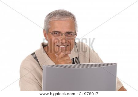 Casually dressed man sitting behind a computer monitor with his chin in his hand isolated on white background