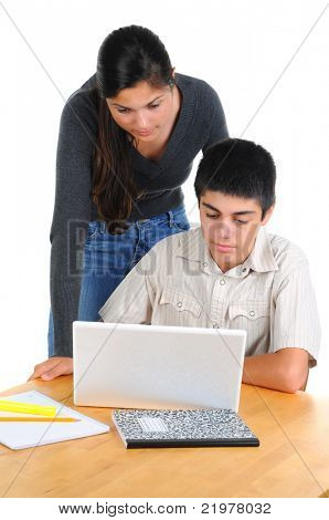 Two students looking at computer. Teenage boy and girl with laptop on their desk. Girl is standing and leaning over seated boy. Vertical format isolated on white.