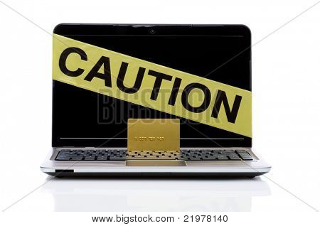 Laptop computer with yellow caution tape and gold credit card isolated on white background with reflection. horizontal format.