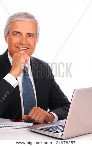 Middle aged businessman seated at his desk in front of laptop computer. Man is smiling with one hand at his chin. Vertical format over white a background.
