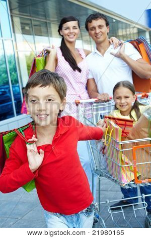 Little boy with sister and parents with shopping bags behind
