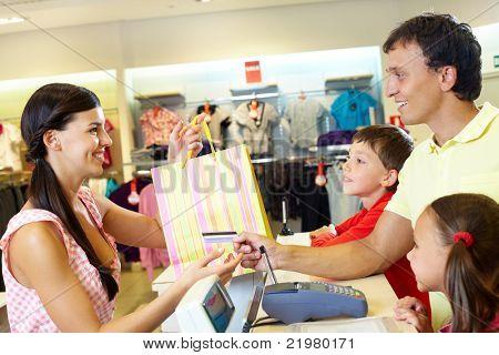 Homem com dois filhos, pagando para compras