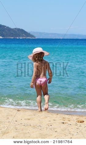 little girl with straw hat walking on beach