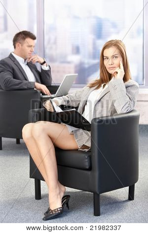 Sexy businesswoman sitting in office lobby during conference break, looking at organizer.