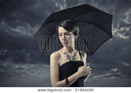 Sad elegant woman under an umbrella with stormy sky in the background
