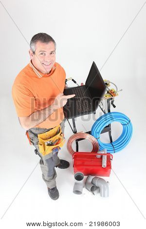 Plumber with tools and a laptop computer with a blank screen