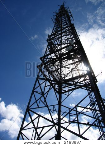 Communications Mast with Blue Sky and White Clouds