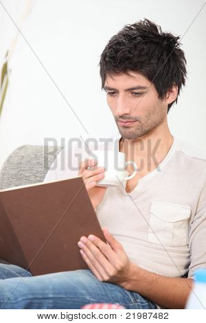 Man drinking a hot drink and reading a book
